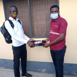 presentation of a laptob and 800ghs to our client in the Anglican university   medical school during the covid